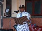 Kepala SMK PGRI 3 Denpasar I Nengah Madiadnyana pada upacara bendera memperingati HUT PGRI Ke-70 dan Hari Guru Nasional 2015 - foto: Koranjuri.com