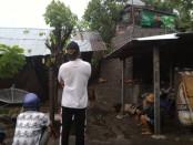 Warga terpaku menatap rumahnya yang rusak akibat terjangan angin kencang - foto: be
