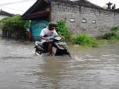Luapan air setinggi sekitar 1,5 meter merendam kawasan  Kepaon, Denpasar, Jum'at (28/06/2013). Air yang meluap hingga sebatas pinggang orang dewasa sampai menggenangi beberapa rumah. Akibatnya, puluhan pengendara sepeda motor terpaksa harus mendorong kendaraannya lantaran mesinnya mati - foto: Wahyu Siswadi/Koranjuri.com