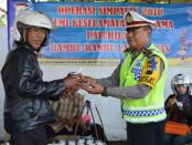 Petugas Satlantas Polres Purworejo membagikan semangkok dawet kepada pengemudi kendaraan dalam operasi Simpatik Candi 2016 - foto: Sujono/Koranjuri.com