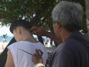 Jasa tato temporer di Pantai Kuta foto: Koranjuri.com