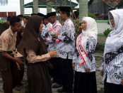 Pemberian bunga dari siswa SMP N 10 kepada para guru, sebagai tanda bakti murid pada guru - foto: Sujono/Koranjuri.com