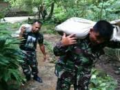 Anggota TNI tengah bekerja keras mengangkut material bedah rumah ke rumah Suroto - foto: Sujono/Koranjuri.com