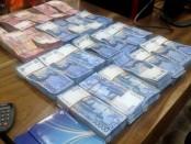 Sejumlah uang hasil dari judi online dijadikan barang bukti oleh Direktorat Reserse Kriminal Umum Polda Bali - foto: Suyanto