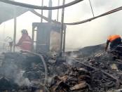 Petugas penjinak api memadamkan sisa api yang masih membakar Gudang Kardus Bekas di jalan Antasura, Denpasar, Minggu, 9 April 2017 pagi - foto: Istimewa