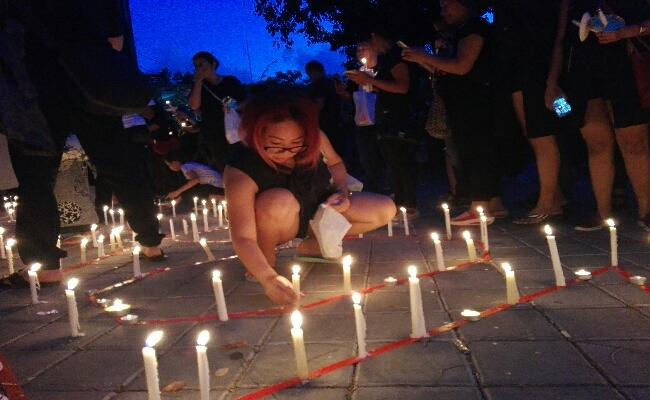 Seorang peserta aksi tengah menyulut lilin di ruang parkir timur Lapangan Puputan Renon - foto: Wahyu Siswadi/Koranjuri.com