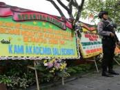 Petugas dari Polda Bali melakukan penjagaan  diantara deretan karangan bunga dukungan penutupan Diskotik Akasaka - foto: Istimewa
