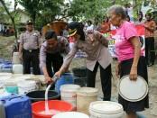 Kapolres Kebumen, AKBP Titi Hastuti saat ikut dalam pembagian air bersih di Desa Kalirejo, Karanggayam, pada kegiatan Polwan peduli, Rabu (30/8) - foto: Sujono/Koranjuri.com