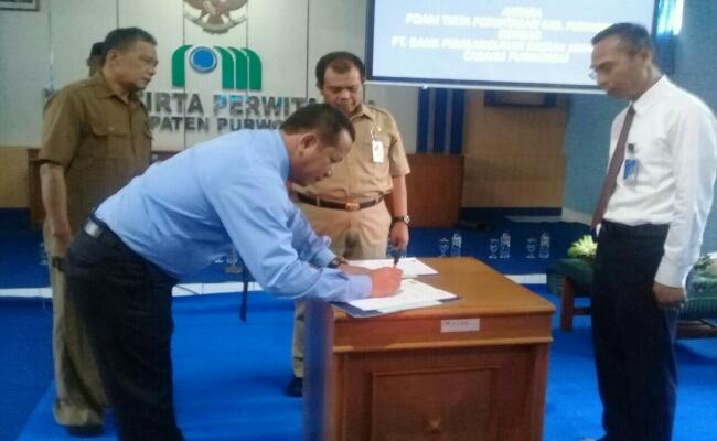 Penandatanganan MoU, antara pimpinan Bank Jateng Cabang Purworejo, Erik Abibon, dengan Direktur PDAM, Hermawan Wahyu Utomo - foto: Sujono/Koranjuri.com
