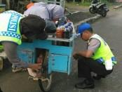 Aksi Bripka Ferin, anggota Polsek Pejagoan, saat membantu memperbaiki sepeda ibu penjual jamu yang rusak, Selasa pagi (19/12) - foto: Sujono/Koranjuri.com