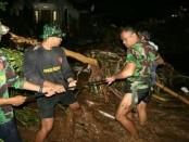 Personel Yonif Raider 900/SBW mengevakuasi warga yang terjebak banjir bandang di Desa Banyuasri, Kota Singaraja, Jumat malam,  27 Januari 2018 - foto: Istimewa