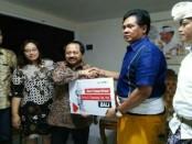 Presdir Smartfren Merza Fachys menyerahkan bantuan secara simbolis untuk pengungsi Gunung Agung melalui Wagub Sudikerta - foto: Ari Wulandari/Koranjuri.com