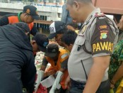Polisi dan warga mengevakuasi jasad bayi yang ditemukan di tumpukan sampah - foto: Istimewa