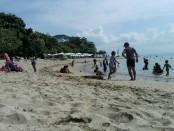 Wisatawan menikmati ketenangan ombak di pantai Karang, Sanur - foto: Koranjuri.com