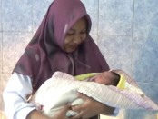 Bayi laki-laki yang ditemukan dalam kardus, dalam gendongan petugas - foto: Sujono/Koranjuri.com