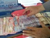 Barang bukti uang yang diamankan dari operasi tangkap tangan yang dilakukan Polres Gianyar di Daerah Tujuan Wisata Tirta Empul, Tampaksiring - foto: Istimewa