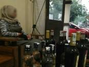 Tersangka ID, dengan barang bukti puluhan botol miras dari berbagai merk - foto: Sujono/Koranjuri.com