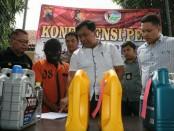 ESW, warga Kuwarasan, Kebumen, tersangka penjual oli palsu, dengan sejumlah barang bukti - foto: Sujono/Koranjuri.com