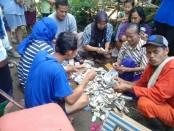 Warga ikut menghitung uang yang ditemukan di tumpukan barang bekas yang tak terpakai, di rumah Sutarman, saat diadakan pembersihan sebelum direhab, Rabu (20/3/2019) - foto: Sujono/Koranjuri.com