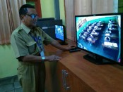 Ki Gandung Ngadino, Kepala SMK TKM Purworejo, saat memantau pelaksanaan USBN melalui layar monitor CCTV - foto: Sujono/Koranjuri.com