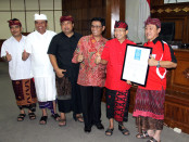 Ketua Indonesia Kennel Klub (IKK) Benny Kwok Wie Sioe bersama Gubernur Bali I Wayan Koster menyerahkan sertifikat pengakuan dunia anjing Kintamani - foto: Istimewa