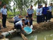 Kadivpas Kanwil Kemenhukham Jawa Tengah, Marasidin Siregar, saat menebar ribuan benih ikan di kolam Kampung Asimilasi Rutan Purworejo, Senin (29/4) lalu, yang terletak di Lugosobo, Gebang, didampingi Karutan Purworejo, Lukman Agung Widodo - foto: Sujono/Koranjuri.com