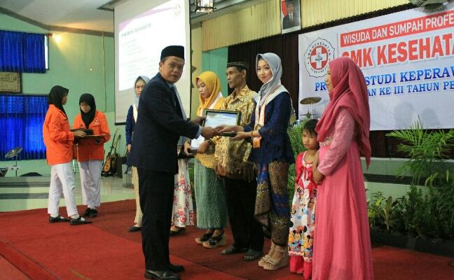 Nuryadin, S.Sos, M.Pd, Kepala SMK Kesehatan Purworejo, saat memberikan penghargaan kepada siswa berprestasi. - foto: Sujono/Koranjuri.com