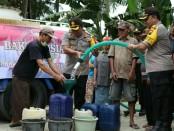 Kapolres Purworejo, AKBP Indra Kurniawan Mangunsong, saat memimpin pendistribusian air bersih di Desa Bendungan, Grabag, Kamis (27/6) - foto: Sujono/Koranjuri.com