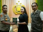Kapolresta Denpasar Kombes Pol Ruddi Setiawan memberikan penghargaan kepada Regina, turis Rusia yang membantu polisi sebagai alih bahasa dari kasus kejahatan yang dilakukan oleh dua orang yang juga berasal dari Rusia - foto: Istimewa