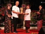 Gubernur Bali Wayan Koster menyerahkan cenderamata kepada Ketua Umum KAGAMA Ganjar Pranowo, yang juga Gubernur Jawa Tengah - foto: Istimewa