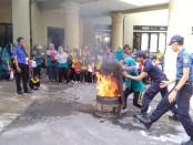 Petugas dari Kantor Satpol PP dan Damkar Kabupaten Purworejo, tampak memberikan pelatihan cara memadamkan api menggunakan karung goni basah, dihadapan siswa, orangtua, dan guru dari TK Wolo Jurutengah, Nambangan, Grabag, Senin (16/12) - foto: Sujono/Koranjuri.com