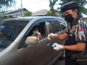 Organisasi Kemasyarakatan PEKAT Indonesia Bersatu DPW Bali membagikan hand sanitizer kepada pengguna jalan - foto: Toto/Koranjuri.com