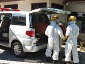Simulasi penguburan jenazah pasien positif Covid-19 ketika dimasukan kedalam mobil jenazah untuk dibawa ke Setra Desa Adat Beng, Rabu (22/4/2020) - foto: Catur/Koranjuri.com