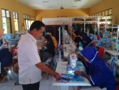Kepala UPT BLK Dinperinaker Kabupaten Purworejo, Sudarman, S.Sos, saat memantau produksi masker yang dikerjakan oleh alumni siswa BLK, Kamis (9/4/2020) - foto: Sujono/Koranjuri.com