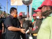Anggota DPR RI I Nyoman Parta saat membagikan paket sembako kepada para petugas kebersihan di Banjar Pinda, Desa Saba, Kecamatan Blahbatuh Gianyar, Jumat (10/4/2020) pagi - foto: Catur/Koranjuri.com