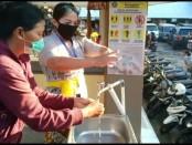 Masyarakat yang sedang mencuci tangan di pintu masuk Pasar Telepud, Desa Sebatu, Tegallalang Gianyar, Senin (13/4/2020) pagi - foto: Catur/Koranjuri.com