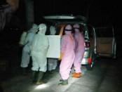 Petugas tengah menurunkan jenasah pasien PDP yang meninggal dari mobil ambulans - foto: Sujono/Koranjuri.com
