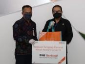 Kepala BNI Wilayah Bali, NTB dan NTT I Made Sukmajaya menyerahkan bantuan paket pangan untuk penanggalan covid-19 di Bali. Bantuan diterima oleh Wagub Bali Tjokorda Oka Artha Ardhana Sukawati - foto: Istimewa