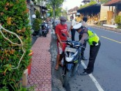 Petugas kepolisian dari Polres Gianyar saat memberikan teguran simpatik kepada pengendara yang melanggar, Senin (1/6/2020) pagi - foto: Catur/Koranjuri.com
