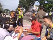 Para pelanggar yang terjaring dalam razia penggunaan masker yang dilakukan tim gabungan, Rabu (3/6) pagi di depan masjid Darul Muttaqien barat alun-alun Purworejo, mendapatkan surat peringatan dari petugas - foto: Sujono/Koranjuri.com