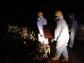 Petugas dari Yonzipur 18/YKR saat melakukan pemulasaran jenazah sesuai dengan protokol pemulasaran jenazah Covid-19 di Setra Desa Adat Medahan, Sabtu (27/6/2020) malam - foto: Catur/Koranjuri.com