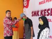 Kepala SMK Kesehatan Purworejo Nuryadin, S.Sos, M.Pd, saat menyematkan topi pada perwakilan peserta, dalam penutupan MPLS di SMK Kesehatan Purworejo, Sabtu (18/07/2020) - foto: Sujono/Koranjuri.com