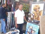 Salah satu pedagang lukisan di Pasar Seni Sukawati, Nyoman Pramadi saat ditemui di tempat berjualannya, Senin (27/7/2020) - foto: Catur/Koranjuri.com