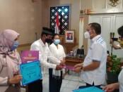 Bupati Purworejo Agus Bastian saat menyerahkan penghargaan kepada perwakilan keluarga tiga ASN yang meninggal saat bertugas, Rabu (02/09/2020) - foto: Sujono/Koranjuri.com