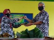 Pemotongan tumpeng, yang dilakukan oleh Kepala SMP N 33 Purworejo, Dr Nikmatur Rohmah, MPd, dan diserahkan kepada Bambang Sukmono Hadi, Kasi PTK dari Dindikpora Kabupaten Purworejo, mewakili kepala dinas, Selasa (06/10/2020) - foto: Sujono/Koranjuri.com