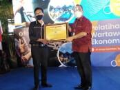 Kepala Perwakilan wilayah Bank Indonesia Provinsi Bali (KPwBI) Trisno Nugroho (kanan) menyerahkan piagam penghargaan kepada Ketua PWI Bali IGMB Dwikora Putra dalam acara Pelatihan Wartawan Ekonomi di Sanur, Denpasar, Jumat (16/10/2020) - foto: Koranjuri.com