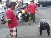 Pecalang atau pengamanan adat di Bali mengawasi warga yang tengah dihukum push up karena melanggar protokol kesehatan setelah terjaring razia - foto: Istimewa