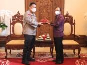 Acara saling bertukar cinderamata antara Gubernur Bali Wayan Koster dan Irjen Pol Petrus Reinhard Golose serta antara Wakil Gubernur Bali Cok Ace dan Irjen Pol Petrus R Golose pun dilakukan - foto: Istimewa