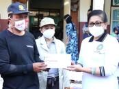 Ketua TP PKK Provinsi Bali Putri Suastini Koster menyerahkan bantuan kepada pengungsi kebakaran yang melanda kawasan pemukiman pengepul barang bekas - foto: Istimewa