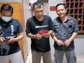 Pelaku (tengah) diamankan setelah mencoba menyelundupkan 100 butir pil happy five ke dalam Lapas - foto: Istimewa